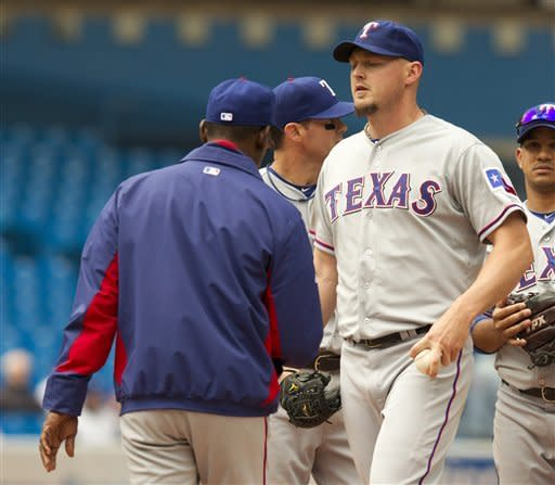 Texas Rangers manager Ron Washington, left foreground, pulls starter Matt Harrison, right foreground, from the game in the fourth inning of a baseball game against the Toronto Blue Jays, in Toronto, Wednesday, May 2, 2012. Others are unidentified. (AP Photo/The Canadian Press, Frank Gunn)