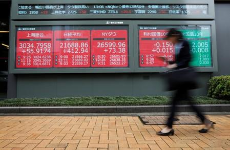 A woman walks past an electric screen showing world markets indices outside a brokerage in Tokyo