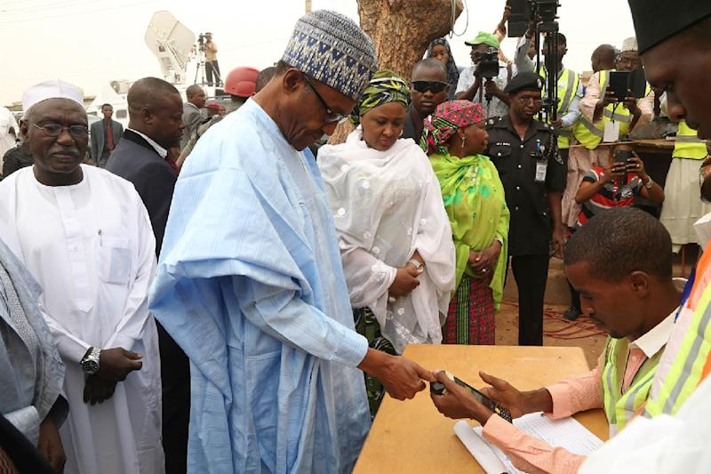 Nigeria's President-elect Muhammadu Buhari completes accreditation for the Governorship and House of Assembly election next to his wife Aisha Buhari in Daura, Katsina State, on April 11, 2015 (AFP Photo/Sunday Aghaeze)