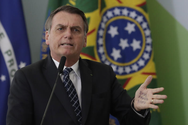 """Brazil's President Jair Bolsonaro's hand shows notes for his speech that read in Portuguese """"God, Family, Brazil,"""" during the launching ceremony of the Doctors for Brazil Program, at the Planalto Presidential Palace, in Brasilia, Brazil, Thursday, Aug. 1, 2019. According to the government, the Doctors for Brazil Program will replace the program implemented by Former President Dilma Rousseff with the help of Cuban doctors, replacing them with Brazilian doctors. (AP Photo/Eraldo Peres)"""
