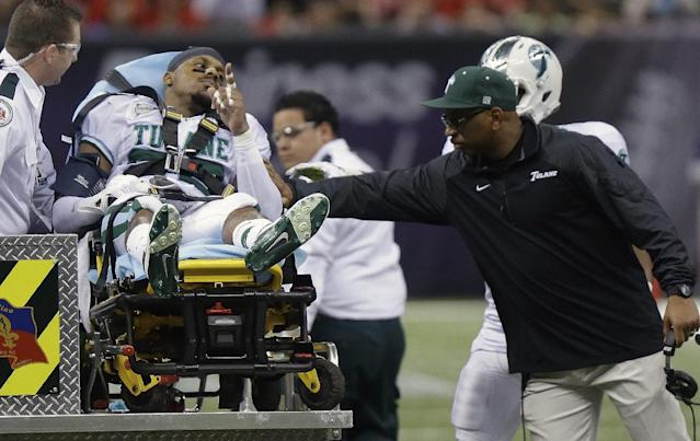 Tulane head coach Curtis Johnson, right, taps Tulane cornerback Jordan Sullen (22) as he leaves the field after being injured in during the second half of the New Orleans Bowl NCAA college football game against Louisiana-Lafayette in New Orleans, Saturday, Dec. 21, 2013. (AP Photo/Bill Haber)