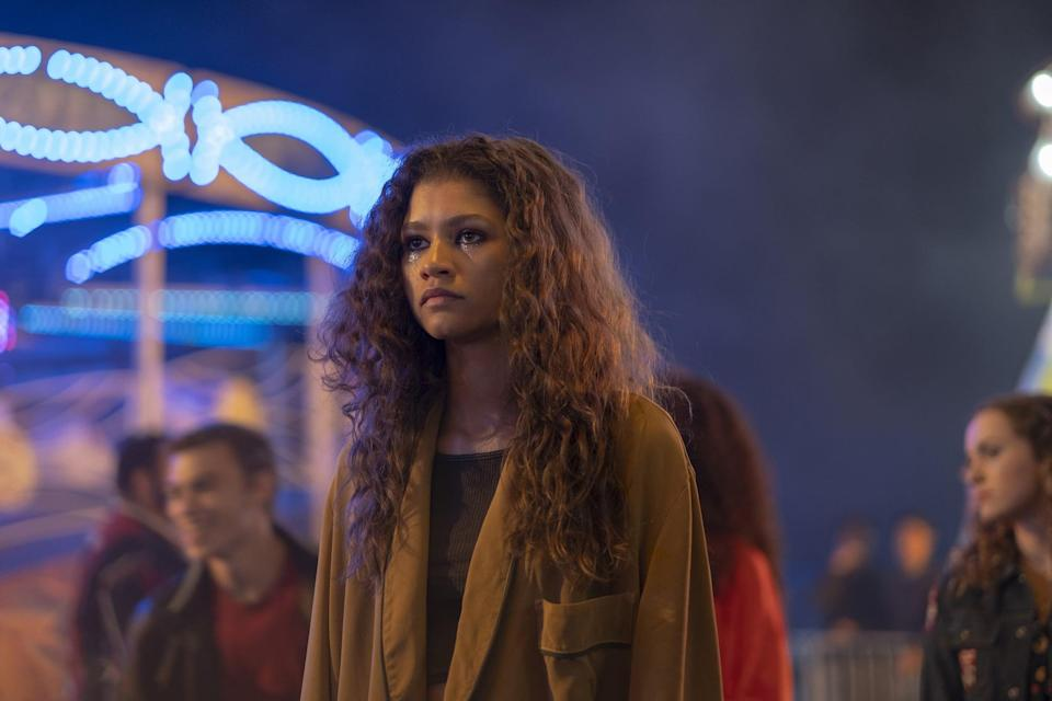 <p>Back at it again with the laid-back banger, Rue's carnival look is all things cool and collected. Her oversize jacket and small crop give this style a teenage twist, while also being a little adult. Rue strives to keep things together, and her outfits reflect that.</p> <p><strong>What to wear</strong>: To pull of this outfit, you'll need a long brown trench coat, small knit crop top, and black jeans. Note here that her makeup is really on point, so be sure to add a little glitter to your look. FYI, you'll need her iconic Converse for this, too.</p>