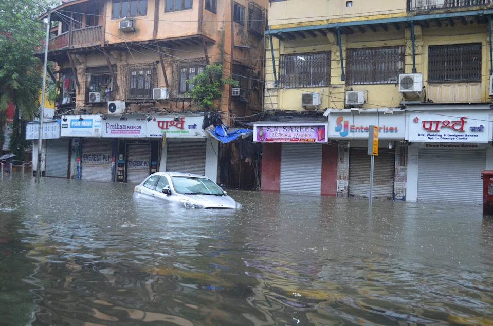 A car is stranded on a heavily flooded road in Mumbai. (Photo by Arun Patil)