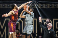 Virginia Tech guard Wabissa Bede (3) fouls Wake Forest guard Daivien Williamson (4) on a three point-attempt as Virginia Tech head coach Mike Young looks during an NCAA college basketball game Sunday, Jan. 17, 2021, in Winston-Salem, N.C. (Andrew Dye/The Winston-Salem Journal via AP)