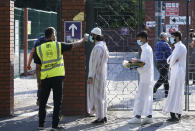 FILE - In this file photo dated Friday, July 31, 2020, people wearing face masks have their temperatures checked before being allowed to go into Manchester Central Mosque, as Muslims worldwide marked the start of the Eid al-Adha holiday, in Manchester, northern England. The British government insists that science is guiding its decisions as the country navigates its way through the coronavirus pandemic. But a self-appointed group of independent experts led by a former government chief adviser says it sees little evidence-based about Britain's response. Unlike other countries, the scientific opposition to Britain's approach is remarkably organized. The independent group sits almost in parallel to the government's own scientists, assesses the same outbreak indicators and has put out detailed reports on issues such contact tracing, reopening schools and pubs, and relaxing social distancing(AP Photo/Jon Super, File)