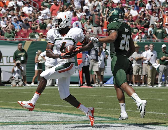 Miami wide receiver Herb Waters (6) pulls in a 19-yard touchdown after getting past South Florida safety Mark Joyce (26) during the first quarter of an NCAA college football game Saturday, Sept. 28, 2013, in Tampa, Fla. (AP Photo/Chris O'Meara)