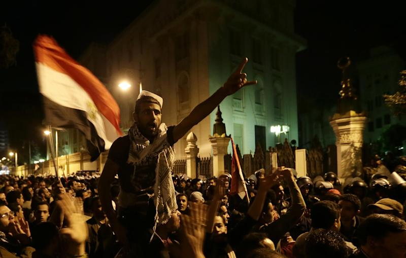 Egyptian protesters chant anti Muslim Brotherhood and Egyptian President Mohammed Mosri slogans outside the presidential palace after they broke a barbed wire barricade keeping them from getting closer to the presidential palace, in Cairo, Egypt, Friday, Dec. 7, 2012. Egypt's political crisis spiraled deeper into bitterness and recrimination Friday as thousands of Islamist backers of the president vowed vengeance at a funeral for men killed in bloody clashes earlier this week and large crowds of the president's opponents marched on his palace to increase pressure after he rejected their demands. (AP Photo/Hassan Ammar)