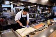 Chef and owner Austin Hu prepares frozen cod fish and salmon at Heritage by Madison restaurant, in Shanghai