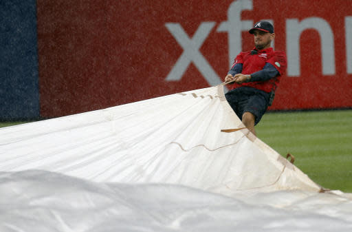 An Atlanta Braves grounds crew member works to cover the infield at Turner Field during a rain shower in the sixth inning of a baseball game against Philadelphia Phillies in Atlanta, Sunday, July 20, 2014.(AP Photo/John Bazemore)