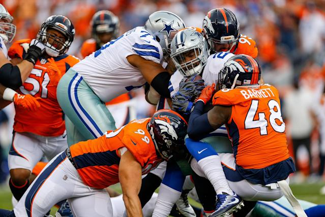 <p>Running back Ezekiel Elliott #21 of the Dallas Cowboys is tackled by Adam Gotsis #99 and outside linebacker Shaquil Barrett #48 of the Denver Broncos int he first quarter of a game at Sports Authority Field at Mile High on September 17, 2017 in Denver, Colorado. (Photo by Justin Edmonds/Getty Images) </p>