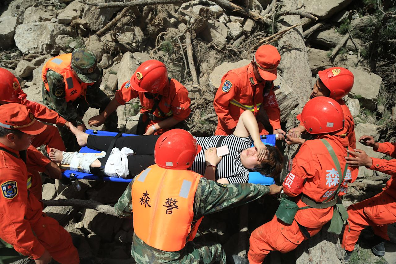 <p>Armed police soldiers carry an injured woman after the 7.0-magnitude earthquake at Jiuzhaigou County on Aug. 9, 2017 in Aba Tibetan and Qiang Autonomous Prefecture, Sichuan Province of China. (Photo: Wang Weishuang/VCG via Getty Images) </p>