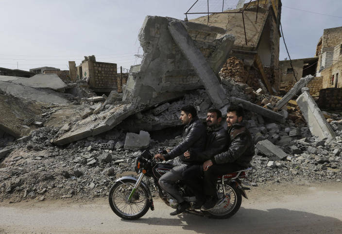A Syrian drives his motor bike past a house destroyed from a government airstrike, at Jabal al-Zaweya village of Sarjeh, in Idlib, Syria, Monday Feb. 25, 2013. Syria is ready to hold talks with the armed opposition trying to topple President Bashar Assad, the country's foreign minister said Monday, in the government's most advanced offer yet to try to resolve the 2-year-old civil war through negotiations. (AP Photo/Hussein Malla)