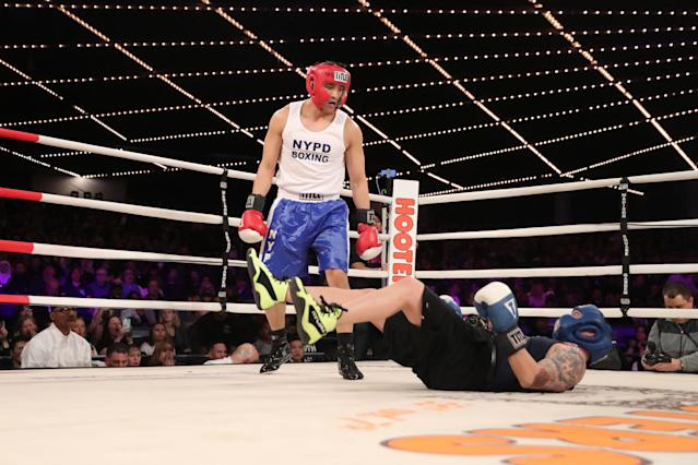 <p>Tom Keung (red) knocks down Mike Almonte (blue) in the Brooklyn Lieutenants Match during the NYPD Boxing Championships at the Hulu Theater at Madison Square Garden on March 15, 2018. (Gordon Donovan/Yahoo News) </p>