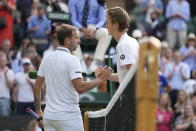 Sebastian Korda of the US shakes hands with Britain's Daniel Evans, left, after winning the men's singles third round match on day five of the Wimbledon Tennis Championships in London, Friday July 2, 2021. (AP Photo/Kirsty Wigglesworth)