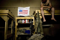 Spc. Dallas Purdy from Hockley, Texas, hangs a message of support from friends Ashley and Katie Daniels while serving with the 1-320th Alpha Battery, 2nd Brigade of the 101st Airborne Division at COP Nolen, in the volatile Arghandab Valley, Kandahar, Afghanistan on July 29, 2010. (AP Photo/Rodrigo Abd, File)
