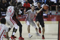 San Diego State's Trey Pulliam (4) drives to the rim against UNLV's Cheikh Mbacke Diong (34) and Nicquel Blake (22) during the second half of an NCAA college basketball game Wednesday, March 3, 2021, in Las Vegas. (AP Photo/Joe Buglewicz)