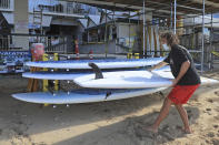 Mitch Kemp, a worker at a Waikiki Beach rental company, readies a paddle board for rental Thursday, Oct. 15, 2020, in Honolulu. The beach rental company opened for the first time Thursday since closing in March due to the COVID-19 pandemic. A new pre-travel testing program will allow visitors who test negative for COVID-19 to come to Hawaii and avoid two weeks of mandatory quarantine goes into effect Thursday. Kemp, who has been unemployed since March, hopes the new testing testing protocol will allow tourists to return. (AP Photo/Marco Garcia)