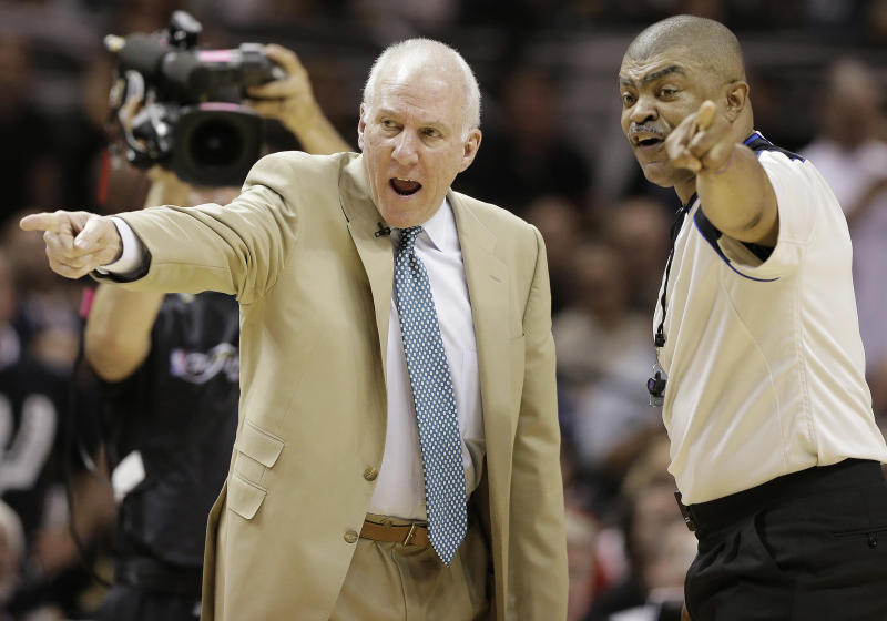 San Antonio Spurs' Gregg Popovich and referee Tony Brothers (25) discuss action during the first half at Game 5 of the NBA Finals basketball series against the Miami Heat, Sunday, June 16, 2013, in San Antonio. (AP Photo/Eric Gay)