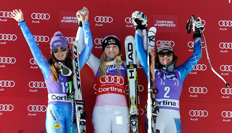 Lindsey Vonn, of the United States, center, winner of an Alpine Ski World Cup women's downhill, celebrates on the podium with second placed Tina Maze, of Slovenia, left, and third placed Leanne Smith, also of the US, in Cortina D'Ampezzo, Italy, Saturday, Jan.19, 2013. (AP Photo/Giovanni Auletta)