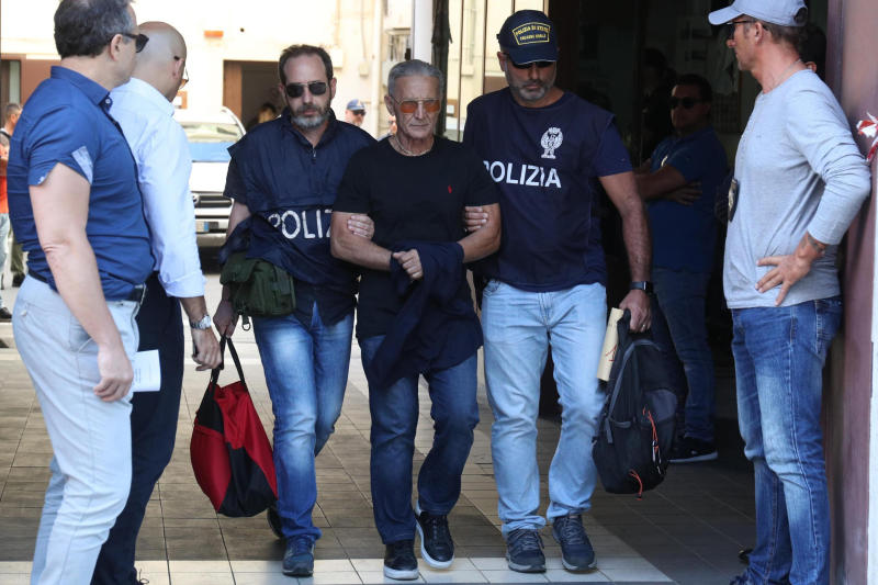 Suspect Rosario Gambino, center, is taken into custody during an anti-mafia operation lead by the Italian Police and the FBI in Palermo, Southern Italy, Wednesday, July 17, 2019. Italian police and the FBI arrested 19 suspected Mafiosi in a joint operation Wednesday following an investigation which revealed alleged ties between Sicily's Cosa Nostra Mafia and New York's Gambino crime family. (Igor Petix/ANSA Via AP)