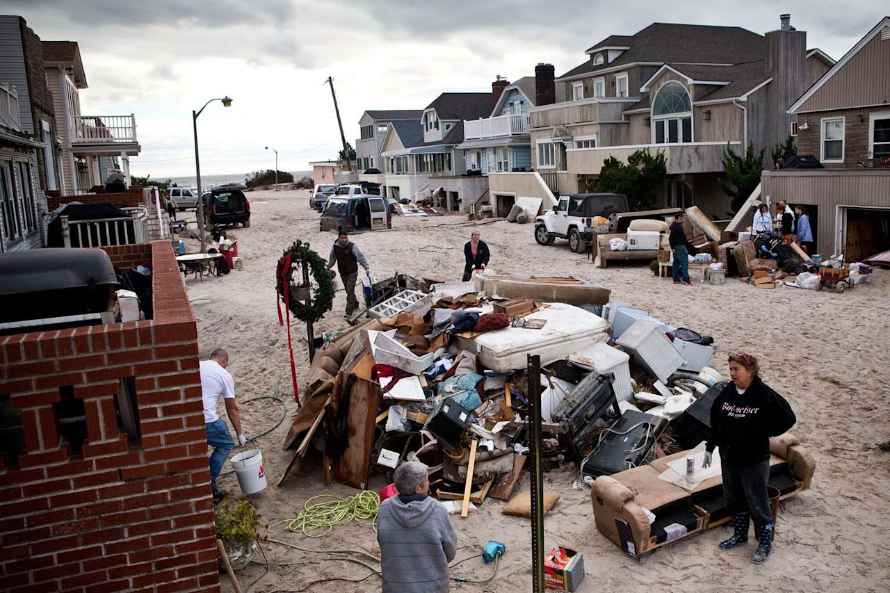 LONG BEACH, NY - OCTOBER 31:  Residents attempt to restore order to their street, which experienced heavy flooding and dune erosion due to Hurricane Sandy, on October 31, 2012 in Long Beach, New York.The storm has claimed many lives in the United States and has caused massive flooding across much of the Atlantic seaboard. U.S. President Barack Obama has declared the situation a 'major disaster' for large areas of the U.S. east coast, including New York City, with widespread power outages and significant flooding in parts of the city.  (Photo by Andrew Burton/Getty Images)