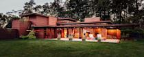 """<p>Frank Lloyd Wright first conceived of this house, located on the shores of Lake Michigan, in the pages of <em>LIFE</em> magazine, when the editors asked him to propose an affordable, middle-class Dream House in the publication's pages. A Wisconsin business man, <a href=""""https://franklloydwright.org/site/bernard-schwartz-house/"""" rel=""""nofollow noopener"""" target=""""_blank"""" data-ylk=""""slk:Bernard Schwartz"""" class=""""link rapid-noclick-resp"""">Bernard Schwartz</a>, commissioned Wright to realize the house and it was completed (with some tweaks) in 1939. </p><p>And luckily today, you can book the house for as long as you want. The four-bedroom home features a 63-foot-long living room, clerestory windows, and warm exposed brick walls. While there are many of Wright's signature fireplaces throughout, you can also enjoy a night out in nature alongside a fire pit.</p><p>Book your stay <a href=""""https://www.airbnb.com/rooms/13783?source_impression_id=p3_1605296178_q0UkdZ7JQm%2F1m%2FUx&guests=1&adults=1"""" rel=""""nofollow noopener"""" target=""""_blank"""" data-ylk=""""slk:here"""" class=""""link rapid-noclick-resp"""">here</a>. </p>"""