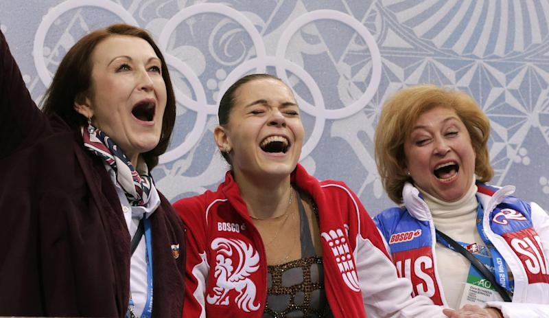 Adelina Sotnikova of Russia, centre, her coach Elena Buianova, right, and choreographer Irina Tagaeva react in the results area after she completed her routine in the women's free skate figure skating finals at the Iceberg Skating Palace during the 2014 Winter Olympics, Thursday, Feb. 20, 2014, in Sochi, Russia. (AP Photo/Bernat Armangue)