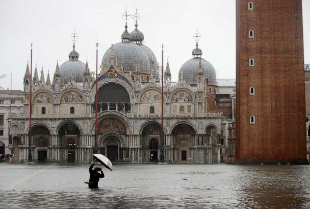 PHOTO: A photographer takes pictures in a flooded St. Mark's Square, in Venice, Italy, Nov. 12, 2019. (Luca Bruno/AP, FILE)