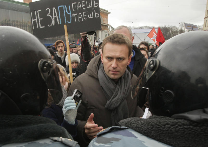 """FILE -  In this file photo taken on Saturday, Feb. 25, 2012, Opposition leader Alexey Navalny,  speaks with riot police officers blocking the way during a massive protest rally against Prime Minister Vladimir Putin's rule in St. Petersburg, Russia. The poster reads: 'We will not be frighten"""". Russian investigators have launched a probe against opposition leader Alexei Navalny, suspecting him of fraud and money laundering. 36-year-old Navalny, one of President Vladimir Putin's fiercest critics, was a driving force behind last winter's wave of anti-Putin rallies. Over the winter, the anti-corruption activist spearheaded a series of rallies in Moscow that drew up to 100,000 people to the streets ahead of the March vote that handed Putin a third presidential term.(AP Photo/Dmitry Lovetsky, File)"""