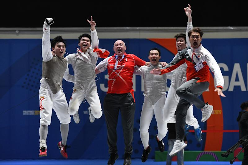 Singapore's men's foil fencers celebrate their team gold with their coach after beating Thailand in the final. (PHOTO: SNOC/Lim Weixiang)