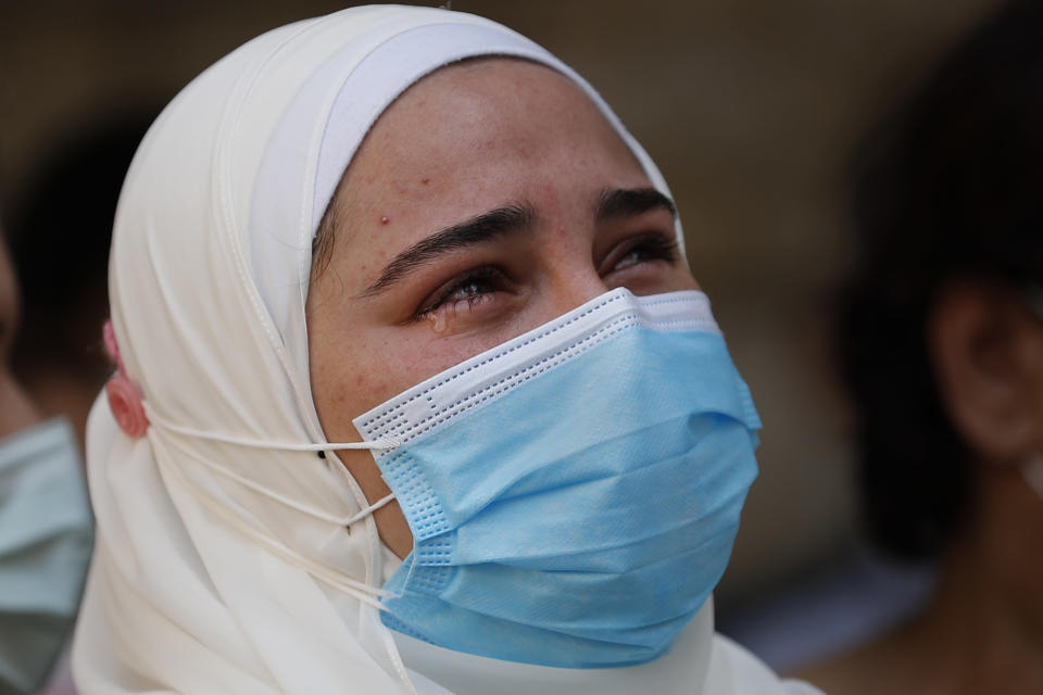 The fiancé of Ibrahim Harb, 35, a Lebanese man who was critically injured in the massive explosion at Beirut's port last year and who died on Monday nearly 14 months after the blast, mourns during his funeral procession in Beirut, Lebanon, Tuesday, Sept. 28, 2021. On Aug. 4, 2020, hundreds of tons of ammonium nitrate, a highly explosive material used in fertilizers, ignited after a massive fire at the port. The death brings to at least 215 the number of people who have been killed by the blast, according to official records. (AP Photo/Hussein Malla)