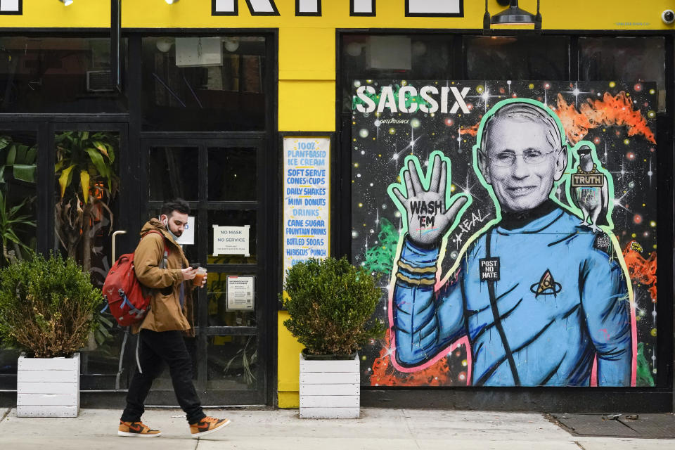 A pedestrian wears his mask below on his chin as he walks past a street art depiction on Dr. Anthony Fauci, Friday, March 26, 2021, in the East Village neighborhood of New York. A year after becoming a global epicenter of the coronavirus pandemic, New York and New Jersey are back atop the list of U.S. states with the highest rates of infection. (AP Photo/Mary Altaffer)