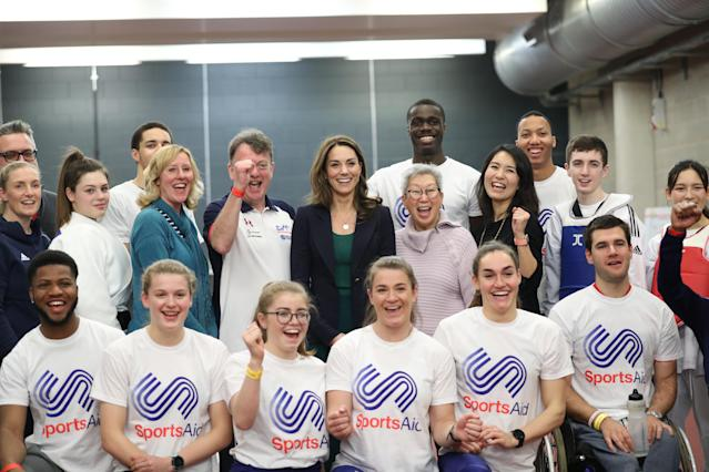 The Duchess of Cambridge (centre) poses for a photograph with young athletes and staff. (Press Association)