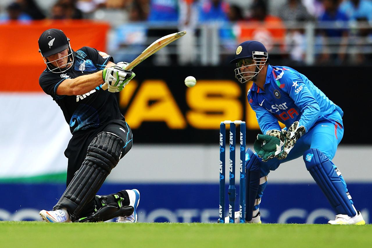 AUCKLAND, NEW ZEALAND - JANUARY 25: Martin Guptill of New Zealand bats as MS Dhoni of India looks on during the One Day International match between New Zealand and India at Eden Park on January 25, 2014 in Auckland, New Zealand.  (Photo by Anthony Au-Yeung/Getty Images)