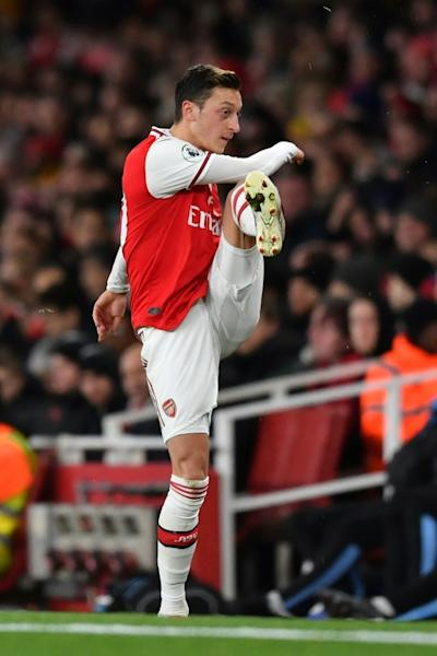 Mesut Ozil reacts to his substitution in Sunday's 3-0 defeat to Manchester City by kicking his gloves away