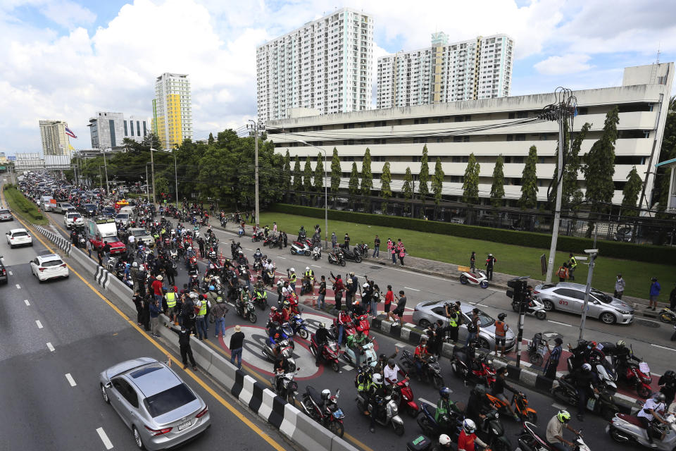 """Anti-government protesters block the road with cars and motorcycles as part of their """"car mob"""" demonstrations along several roads in Bangkok, Thailand, Sunday, Aug. 29, 2021. A long line of cars, trucks and motorbikes wended its way Sunday through the Thai capital Bangkok in a mobile protest against the government of Prime Minister Prayuth Chan-ocha. The protesters on wheels hope their nonviolent action, dubbed a """"car mob,"""" can help force the ouster of Prayuth, whom they accuse of botching the campaign against the coronavirus. (AP Photo/Anuthep Cheysakron)"""