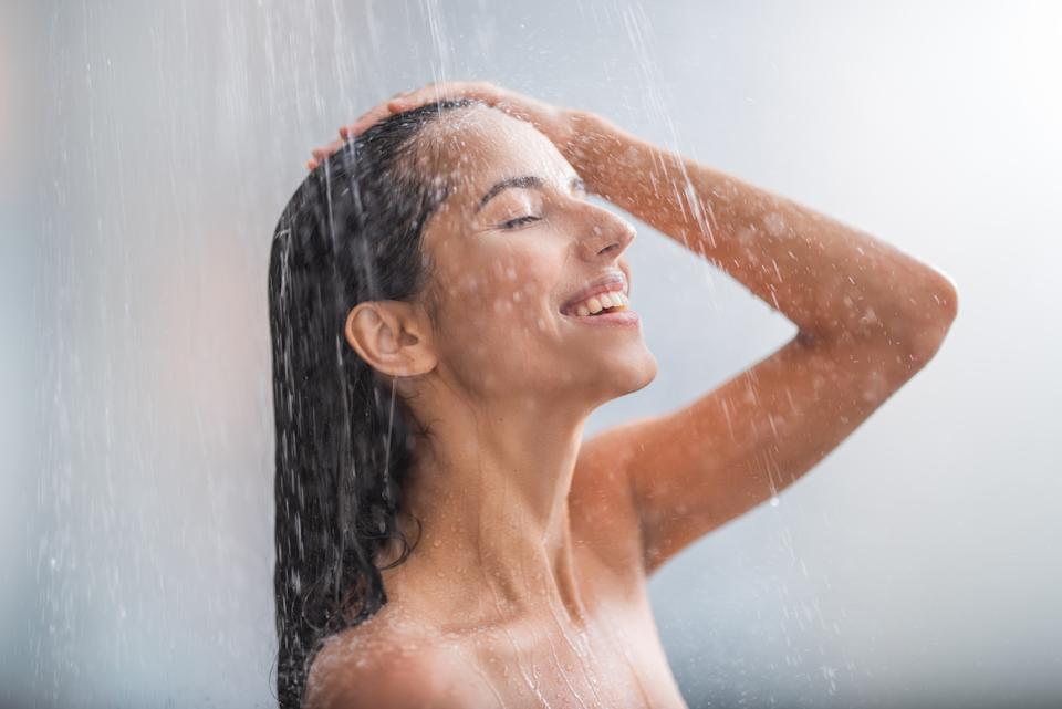 Side view beaming lady locating under stream of water. She holding hair with arms