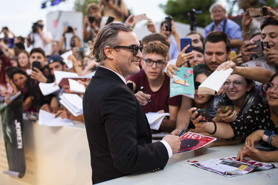 Joaquin Phoenix signs autographs upon arrival at the premiere of the film 'Joker' at the 2019 edition of the Venice Film Festival. (Photo by Arthur Mola/Invision/AP)