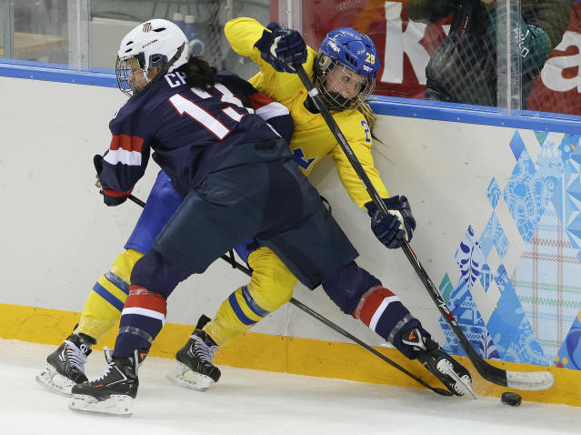 Julie Chu of the United States crashes the boards against Michelle Lowenhielm of Sweden during the third period of the 2014 Winter Olympics women's semifinal ice hockey game at Shayba Arena, Monday, Feb. 17, 2014, in Sochi, Russia. (AP Photo/Matt Slocum)