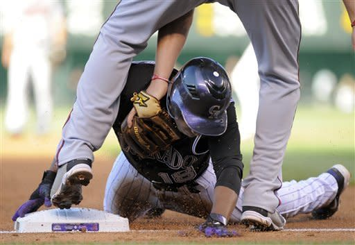 Colorado Rockies' Jonathan Herrera beats the tag by Atlanta Braves' Chipper Jones to steal third during the first inning of a baseball game, Friday, May 4, 2012, in Denver. (AP Photo/Jack Dempsey)