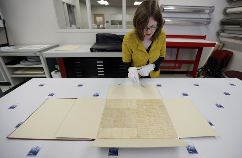 "Archivist Sarah Norris handles William Barret Travis' famed ""Victory of Death"" letter at the Texas State Library and Archives Commission, Wednesday, Feb. 13, 2013, in Austin, Texas. For the first time in 177 years, Travis'  letter addressed to ""the People of Texas and All Americans in the World"" seeking aid to the besieged Texans he commanded at the Alamo will return to the Alamo for display. (AP Photo/Eric Gay)"