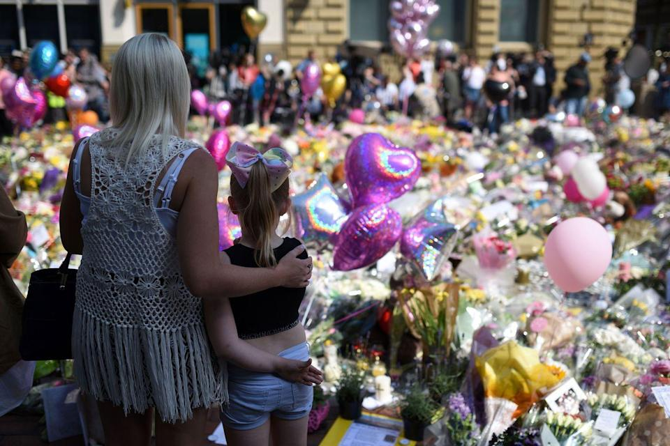<p>People gather to see flowers and messages of support in St. Ann's Square in Manchester, northwest England, placed there in tribute to the victims of the May 22 terror attack at the Manchester Arena.</p>
