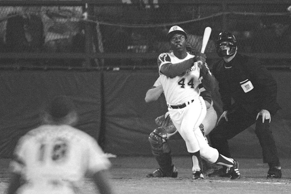 FILE - Atlanta Braves' Hank Aaron eyes the flight of the ball after hitting his 715th career homer in a game against the Los Angeles Dodgers in Atlanta, Ga., in this April 8, 1974 file photo. Dodgers pitcher Al Downing, catcher Joe Ferguson and umpire David Davidson look on. Hank Aaron, who endured racist threats with stoic dignity during his pursuit of Babe Ruth but went on to break the career home run record in the pre-steroids era, died early Friday, Jan. 22, 2021. He was 86. The Atlanta Braves said Aaron died peacefully in his sleep. No cause of death was given. (AP Photo/Harry Harrris, FIle) ORG XMIT: NY156