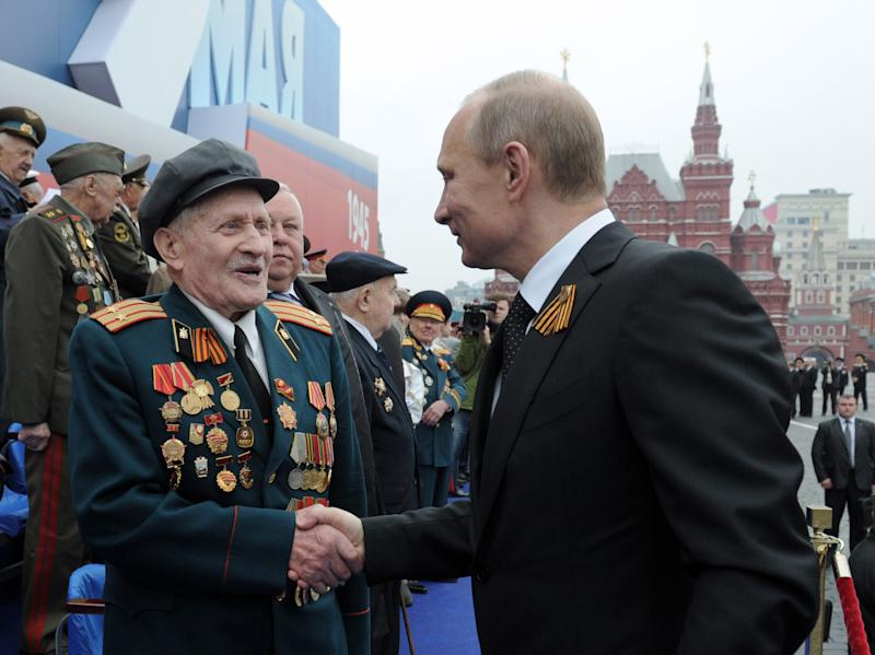 Russian President Vladimir Putin, right, shakes hands with a WWII veteran on the Red Square, during the Victory Day Parade, which commemorates the 1945 defeat of Nazi Germany in Moscow, Russia, Wednesday, May 9, 2012. Russian President Vladimir Putin has told the annual massive military parade in Red Square that the country will stand up for its positions. (AP Photo/RIA Novosti, Alexei Druzhinin, Government Press Service)