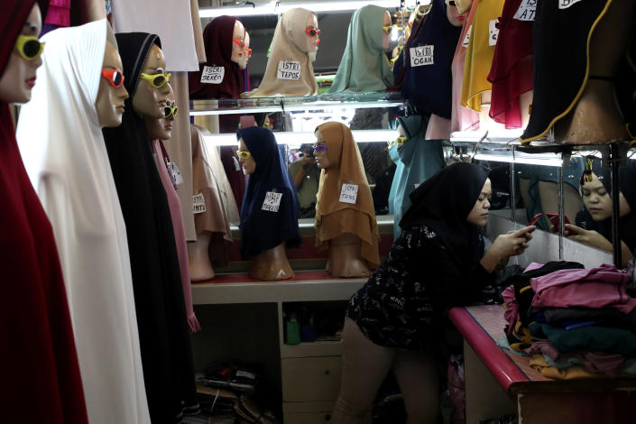 An employee uses her mobile phone as she waits for customers at a shop selling Muslim women's headscarves at a market in Jakarta, Indonesia, Wednesday, Nov. 11, 2020. As companies race to develop a COVID-19 vaccine and countries scramble to secure doses, questions about the use of pork products — banned by some religious groups — has raised concerns about the possibility of disrupted immunization campaigns. (AP Photo/Tatan Syuflana)