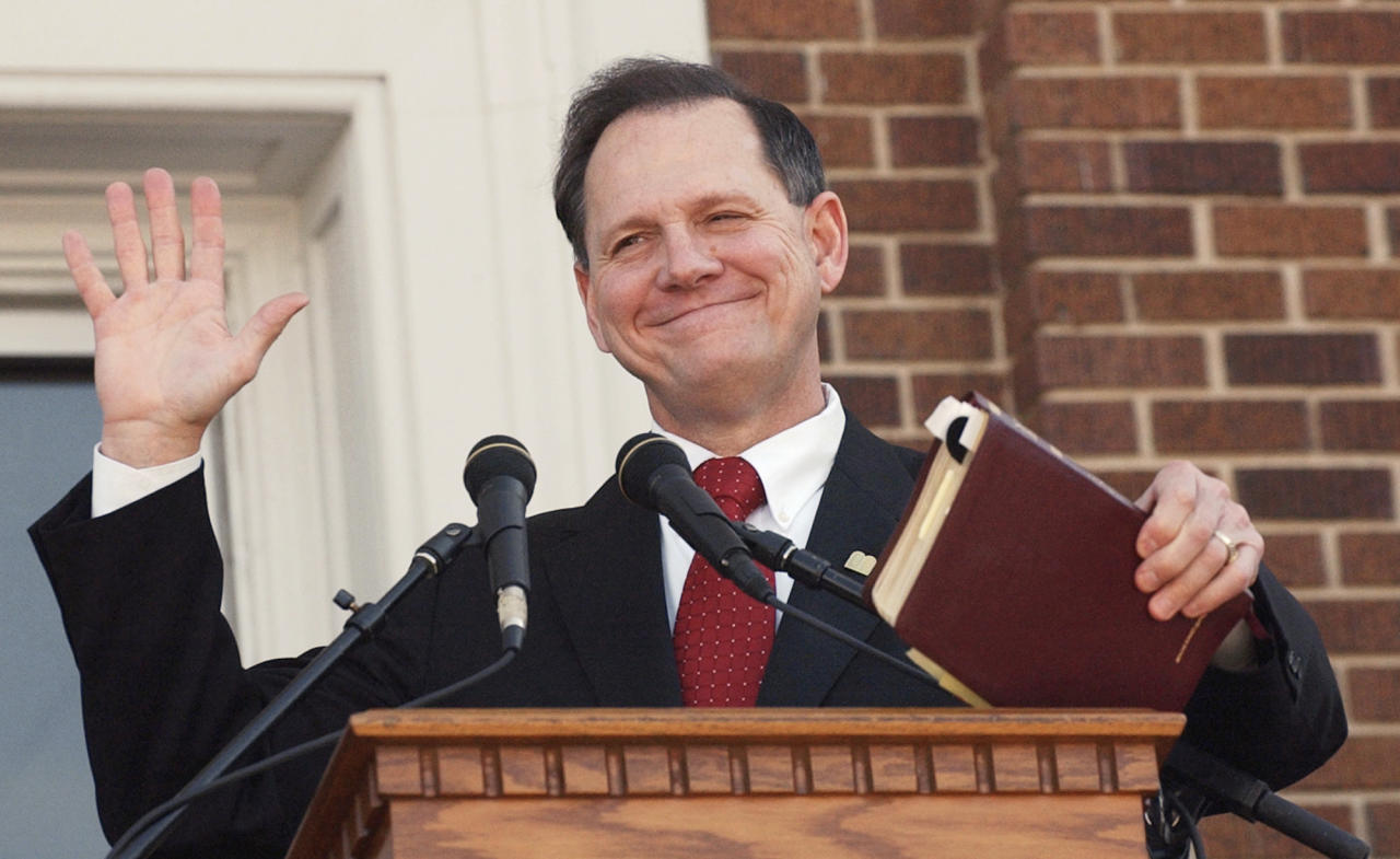 FILE - In this Nov. 6, 2003 file photo, former Alabama Chief Justice Roy Moore holds his Bible as he acknowledges the applause during his speech at the Barrow County Court House in Winder, Ga. Republican Moore's campaign is lashing out again at the news media and accusations of sexual misconduct, but refusing to answer reporters' questions. (AP Photo/Ric Feld, File)