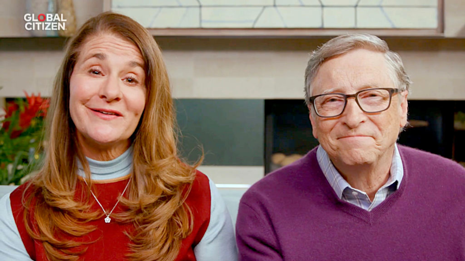 Melinda and Bill Gates sitting on a couch and smiling at the camera.