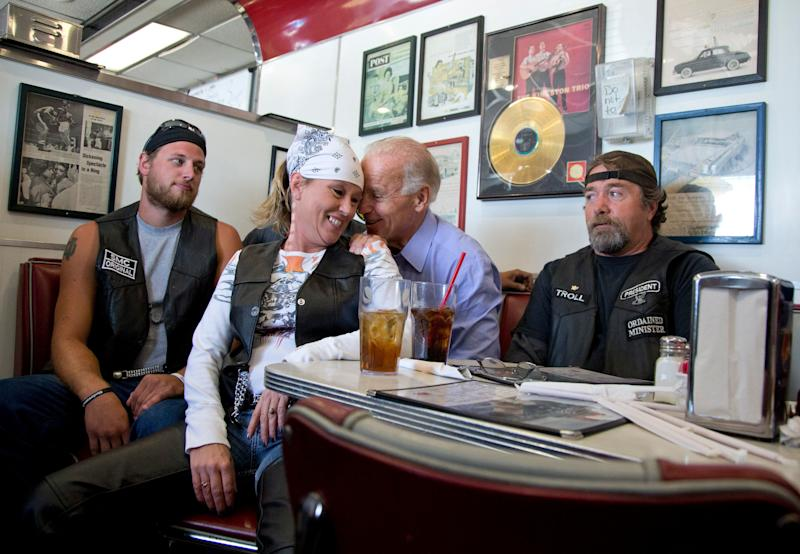 Then-Vice President Joe Biden talks to customers, including a woman who pulled up her chair in front of the bench Biden was sitting on, during a stop at Cruisers Diner in Seaman, Ohio, Sept. 9, 2012. (AP Photo/Carolyn Kaster, File)