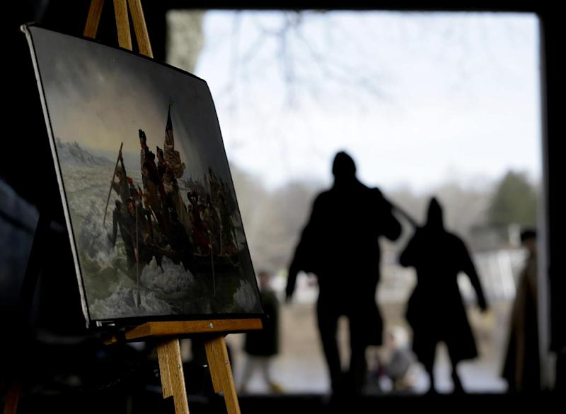 A print of a painting depicting Gen. George Washington's troops crossing the Delaware River in 1776 is displayed in a boathouse as actors carry oars during the 61st annual re-enactment of Washington's daring Christmas 1776 crossing of the river, the trek that turned the tide of the Revolutionary War, in Washington Crossing, N.J. During the crossing 237 years ago, boats ferried 2,400 soldiers, 200 horses and 18 cannons across the river, and the troops marched eight miles downriver before battling Hessian mercenaries in the streets of Trenton. (AP Photo/Julio Cortez)