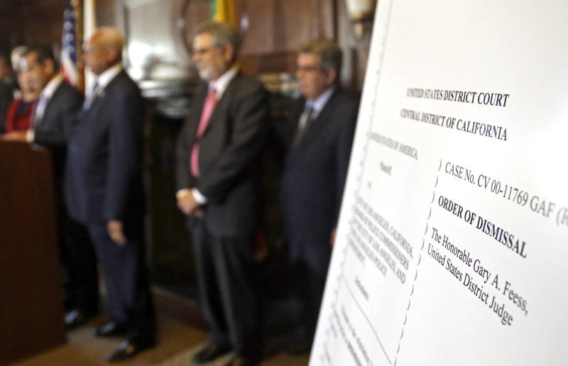 An poster with an enlarged view of the dismissal of the 2001 Los Angeles Police Department consent decree, ending federal oversight of the department prompted by the Rampart corruption scandal, is seen as  the mayor, police chief, and police commission board members appear at police headquarters, Thursday, May 16, 2013, in Los Angeles. (AP Photo/Reed Saxon).